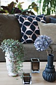 Foliage plant in vintage plant pot, hydrangea in vase and tealight holders on table in front of sofa with scatter cushions