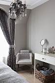 Upholstered chair next to gathered curtain in corner of bedroom painted pale grey; modern console table with cosmetic mirror to one side