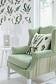 Armchair with pale green, patterned cover and scatter cushion next to white side table with table lamp; fern-patterned wallpaper