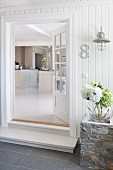 Open front door of white wooden house with view into kitchen area in interior