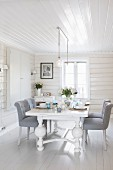 White table with carved feet and chairs upholstered in pale grey in white, wood-clad dining room