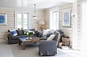 Grey armchair and sofa around rustic wooden coffee table in wood-clad living area
