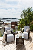 Wicker chairs with white cushions and wicker coffee table on wooden terrace with view of town and sea in background