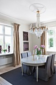 Chairs with grey loose covers around neo-classical dining table below chandelier hanging from stucco ceiling rose in traditional dining room