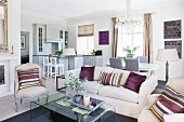 Lounge area with striped scatter cushions on pale sofa and Rococo-style armchairs in open-plan interior