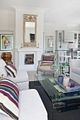 Pale sofa with striped scatter cushions, curved glass coffee table and Rococo armchair in front of fireplace in open-plan interior