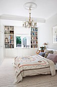 Double bed with patterned bedspread and many scatter cushions, custom shelving and base units around window in background