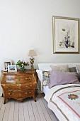 Kommode im Rokoko-Stil neben Bett, auf hellem Dielenboden in ländlichem Schlafzimmer
