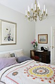 Patterned blanket on double bed with stack of scatter cushions against headboard; antique desk in background