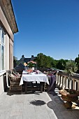 Rattan chairs around table set with white tablecloth on sunny balcony with stone balustrade