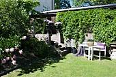 Weisser Tisch und Bank vor berankter Mauer auf Rasen im Garten, seitlich Treppenaufgang