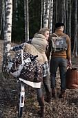 Frau und Mann im herbstlichen Wald unterwegs mit Picknick Ausrüstung und Fahrrad