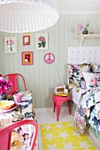 Bed and table in small room with floral textiles, hot pink retro chairs and accessories