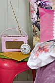 Pink retro radio and alarm clock on pink vintage stool and bed linen with large floral pattern