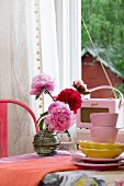 Vintage accessories in shades of pink and red with stacked crockery, retro radio and vase of peonies