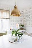 Drehbare Platte mit Blumensträussen und Windlichtern auf rundem, weißem Tisch im Esszimmer