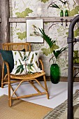 Grass-patterned cushion on bamboo chair in front of green floor vase in front of half-timbered wall with leaf-patterned wallpaper panels in vintage ambiance