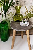Green carafe and drinking glass on vintage wooden stool next to emerald-green floor vase against wall with leaf-patterned wallpaper