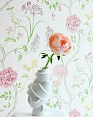 Apricotfarbene Rose in weisser Schnörkel Vase auf Ablage, vor Wand mit floral gemusterter Tapete in Pastelltönen