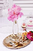 Peonies in crystal vase and cutlery on silver tray