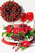 Festive arrangement in red with roses & candle in glass bowl
