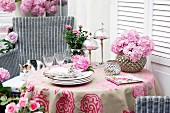 Table on terrace decorated with pink roses & mophead hydrangeas