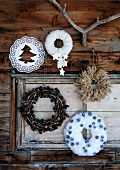 Hand-crafted, decorative Christmas wreaths made from various materials hanging on rustic facade of wooden cabin