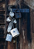 Pine cones dipped in white paint and painted cans hung on rustic cabin door as Christmas decorations
