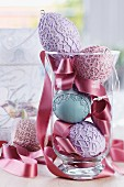 Easter arrangement of ceramic eggs with various lacy patterns and satin ribbon in glass vase