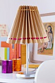 Table lamp with lampshade hand-crafted from brown paper and satin ribbons