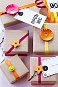 Gift boxes with brown paper lids decorated with buttons, ribbons & tags