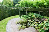 Lily pond and paved area surrounded by lawns and box hedges