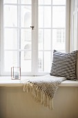 Cushion with black and white cover and fringed blanket next to candle lantern on window sill