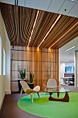 Classic easy chairs with pale upholstery and coffee table on grey carpet with green circle in foyer; slatted wooden wall merging into ceiling area