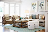 Lounge area with white, drum-shaped stools, wicker armchairs and sofa with scatter cushions around wicker coffee table and pastel blue, patterned rug; floral pictures on wall