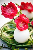 Red peach blossom in miniature vases made from eggshells