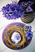 Easter egg decorated with purple napkin decoupage viola in straw nest