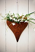Spring wall decoration with snowdrops in heart-shaped vessel