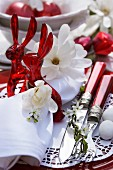 Easter place setting in red and white with rabbit-shaped napkin rings & Magnolia stellata flowers