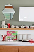 Kitchen counter with white worksurface, storage jars next to child's drawing and various ceramic bowls on white wooden shelf on grey-painted wall