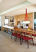 Island counter with extended table top and classic-style, dark wood chairs with red mesh seats in open-plan kitchen