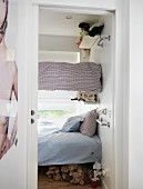 View into tiny bedroom with children's bunk beds anchored in walls in front of window and collection of soft toys under lowest bunk