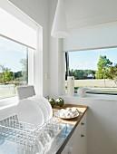 Spülkorb mit Tellern auf der Edelstahlfläche einer einfachen Küchenzeile vor Fenster mit Rollo