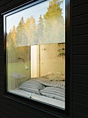 Swedish wooden house; trees reflected in bedroom window and view of bed
