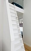 Narrow white staircase leading to mezzanine