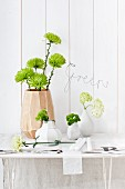 Various vases of chrysanthemums, sweet William, carnations and viburnum; bent wire spelling 'Green' on wall