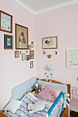 Soft toys on child's bed in corner below framed pictures on pink-painted walls