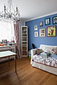 Armchair bed with scatter cushions below framed pictures on blue-painted wall, desk below window
