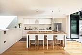 Barhocker mit weissen Hussen vor Küchenblock in offener Designerküche, seitlich geöffnete Terrassen Falttür