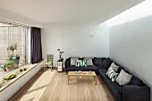 Eckcouch mit grauem Stoffbezug in minimalistischer Wohnraum mit Dielenboden und Panoramafenster mit eingebauter Bank